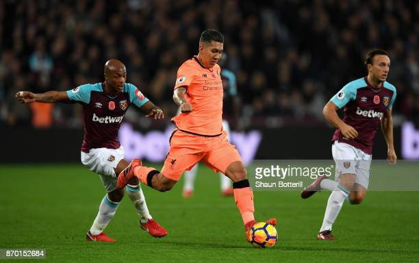Andre Ayew of West Ham United and Roberto Firmino of Liverpool in action during the Premier League match between West Ham United and Liverpool at...