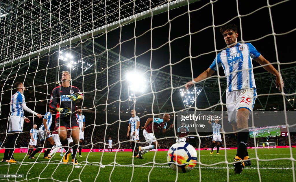 Andre Ayew of West Ham United (C) celebrates as he scores their second goal as Christopher Schindler of Huddersfield Town collects the ball in the net during the Premier League match between West Ham United and Huddersfield Town at London Stadium on September 11, 2017 in London, England.