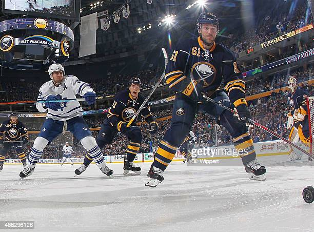 Andre Benoit of the Buffalo Sabres chases the puck into the corner while being pursued by Joffrey Lupul of the Toronto Maple Leafs on April 1 2015 at...