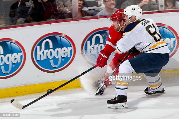 Andre Benoit of the Buffalo Sabres checks Johan Franzen of the Detroit Red Wings into the boards during a NHL game on December 23 2014 at Joe Louis...