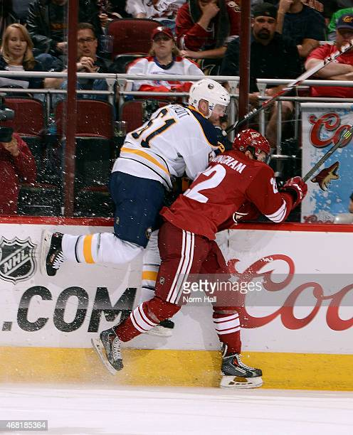 Andre Benoit of the Buffalo Sabres is checked into the boards by Craig Cunningham of the Arizona Coyotes during the second period at Gila River Arena...