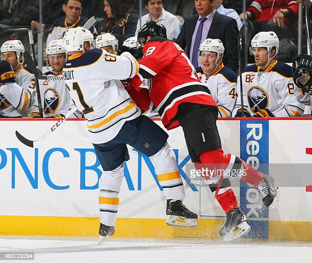 Andre Benoit of the Buffalo Sabres is checked near the boards by Steve Bernier of the New Jersey Devils during the game at the Prudential Center on...