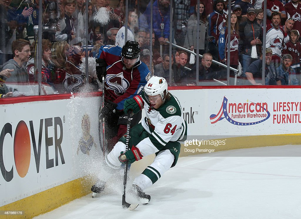 Andre Benoit #61 of the Colorado Avalanche and Mikael Granlund #64 of the Minnesota Wild battle for control of the puck in Game Seven of the First Round of the 2014 NHL Stanley Cup Playoffs at Pepsi Center on April 30, 2014 in Denver, Colorado. The Wild defeated the Avalanche in overtime 5-4 to win the series.