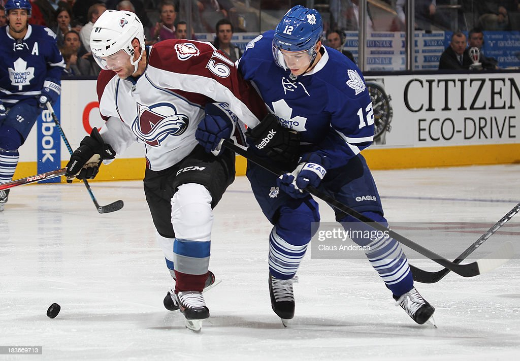 Andre Benoit #61 of the Colorado Avalanche skates against <a gi-track='captionPersonalityLinkClicked' href=/galleries/search?phrase=Mason+Raymond&family=editorial&specificpeople=4521385 ng-click='$event.stopPropagation()'>Mason Raymond</a> #12 of the Toronto Maple Leafs during an NHL game at the Air Canada Centre on October 8, 2013 in Toronto, Ontario, Canada. The Avalanche defeated the Leafs 2-1.