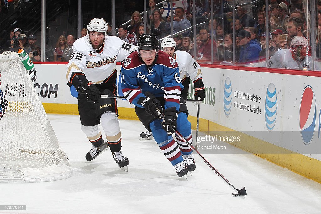 Andre Benoit #61 of the Colorado Avalanche skates with the puck as he is pursued by Patrick Maroon #62 of the Anaheim Ducks at the Pepsi Center on March 14, 2014 in Denver, Colorado.