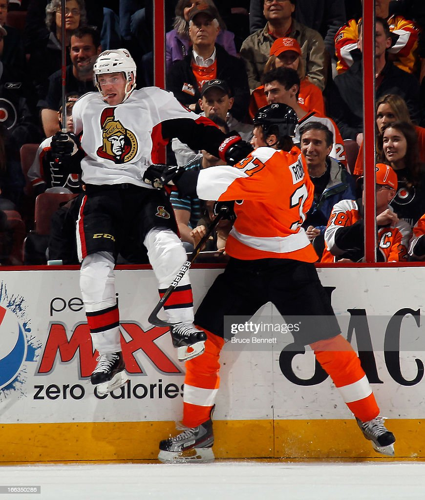 Andre Benoit #61 of the Ottawa Senators and Jay Rosehill #37 of the Philadelphia Flyers hit the boards at the Wells Fargo Center on April 11, 2013 in Philadelphia, Pennsylvania. The Senators defeated the Flyers 3-1.