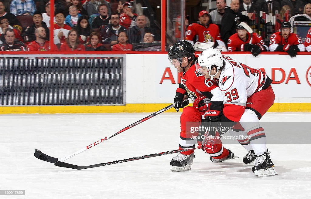 Andre Benoit #61 of the Ottawa Senators beats Patrick Dwyer #39 of the Carolina Hurricanes to the loose puck to prevent a breakaway, during an NHL game at Scotiabank Place on February 7, 2013 in Ottawa, Ontario, Canada.