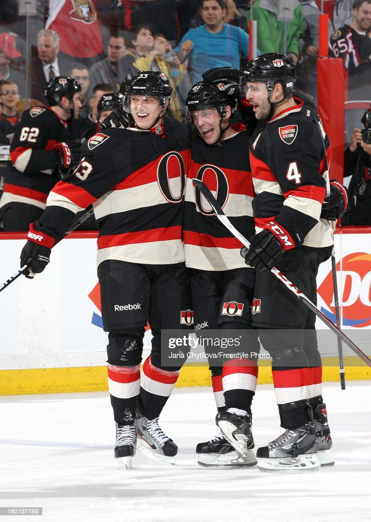Andre Benoit #61 of the Ottawa Senators celebrates his first career NHL goal with team mates Jakob Silfverberg #33 and Chris Phillips #4, during an NHL game against the New York Islanders, at Scotiabank Place on February 19, 2013 in Ottawa, Ontario, Canada.