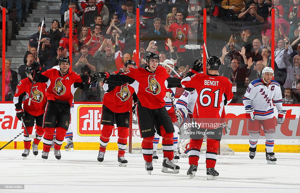 Andre Benoit #61 of the Ottawa Senators celebrates his second-period goal with teammates Chris Phillips #4 and <a gi-track='captionPersonalityLinkClicked' href=/galleries/search?phrase=Mika+Zibanejad&family=editorial&specificpeople=7832310 ng-click='$event.stopPropagation()'>Mika Zibanejad</a> #93 as <a gi-track='captionPersonalityLinkClicked' href=/galleries/search?phrase=Ryan+Callahan&family=editorial&specificpeople=809690 ng-click='$event.stopPropagation()'>Ryan Callahan</a> #24 of the New York Rangers skates away on March 28, 2013 at Scotiabank Place in Ottawa, Ontario, Canada.