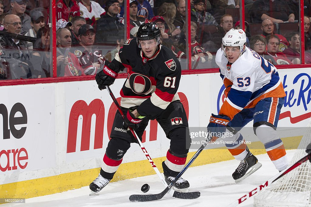 Andre Benoit #61 of the Ottawa Senators defends against a forechecking Casey Cizikas #53 of the New York Islanders during an NHL game at Scotiabank Place on February 19, 2013 in Ottawa, Ontario, Canada.