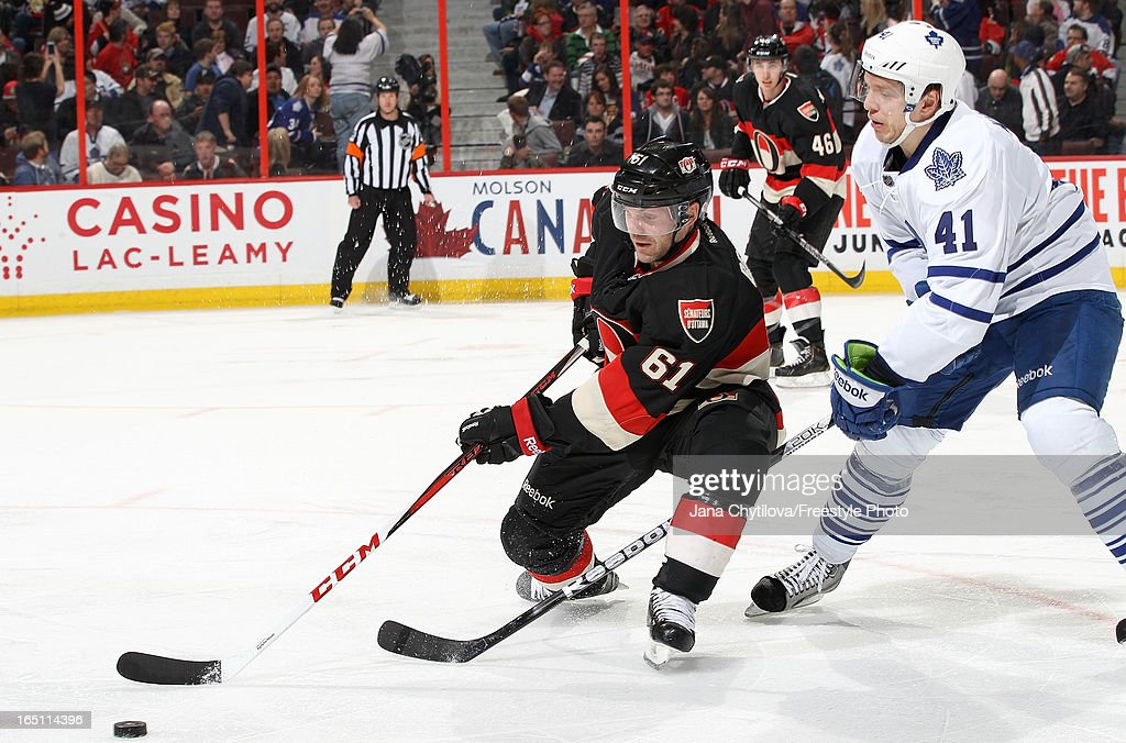 Andre Benoit #61 of the Ottawa Senators fights for the puck against <a gi-track='captionPersonalityLinkClicked' href=/galleries/search?phrase=Nikolai+Kulemin&family=editorial&specificpeople=537949 ng-click='$event.stopPropagation()'>Nikolai Kulemin</a> #41 of the Toronto Maple Leafs, during an NHL game at Scotiabank Place, on March 30, 2013 in Ottawa, Ontario, Canada.