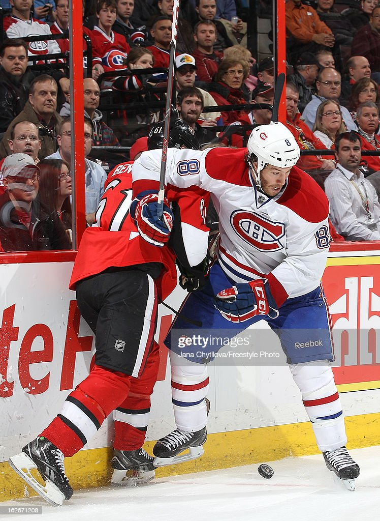 Andre Benoit #61 of the Ottawa Senators gets checked by Brandon Prust #8 of the Montreal Canadiens as they battle for the puck, during an NHL game at Scotiabank Place on February 25, 2013 in Ottawa, Ontario, Canada.