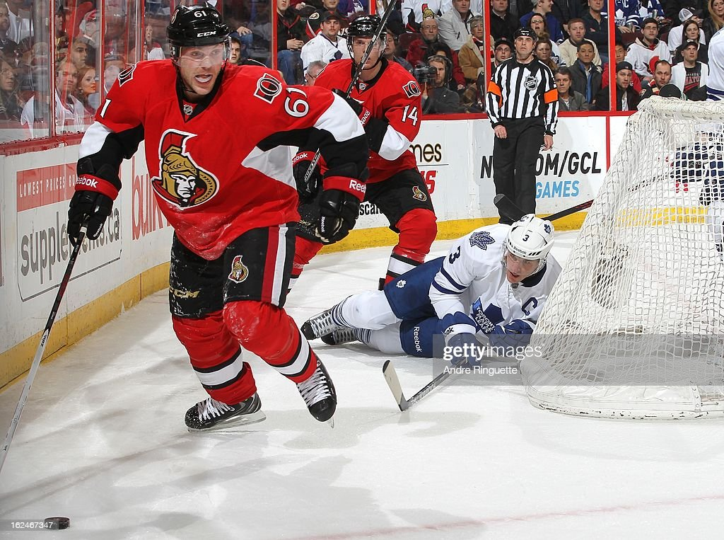 Andre Benoit #61 of the Ottawa Senators skates the puck away from Dion Phaneuf #3 of the Toronto Maple Leafs on February 23, 2013 at Scotiabank Place in Ottawa, Ontario, Canada.