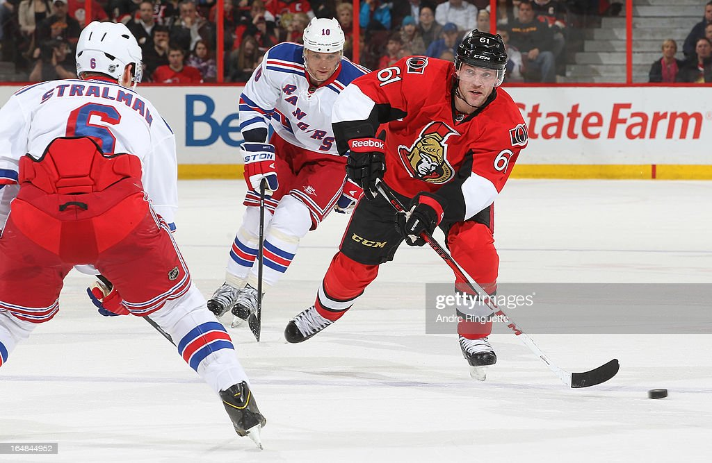 Andre Benoit #61 of the Ottawa Senators skates up ice with the puck against Anton Stralman #6 and <a gi-track='captionPersonalityLinkClicked' href=/galleries/search?phrase=Marian+Gaborik&family=editorial&specificpeople=202477 ng-click='$event.stopPropagation()'>Marian Gaborik</a> #10 of the New York Rangers on March 28, 2013 at Scotiabank Place in Ottawa, Ontario, Canada.