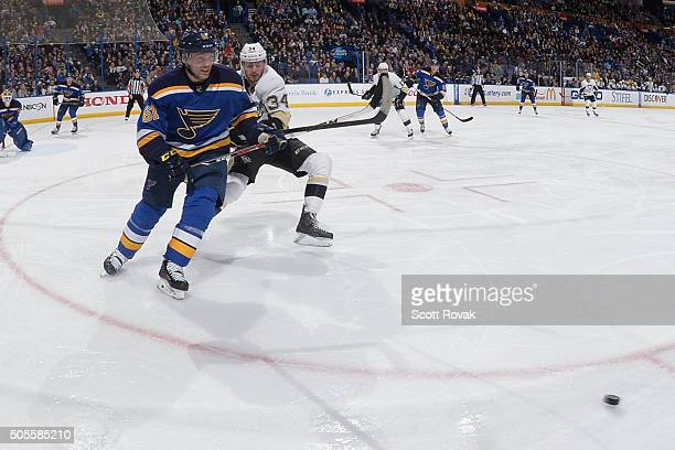 Andre Benoit of the St Louis Blues and Tom Kuhnhackl of the Pittsburgh Penguins race to the puck at the Scottrade Center on January 18 2016 in St...