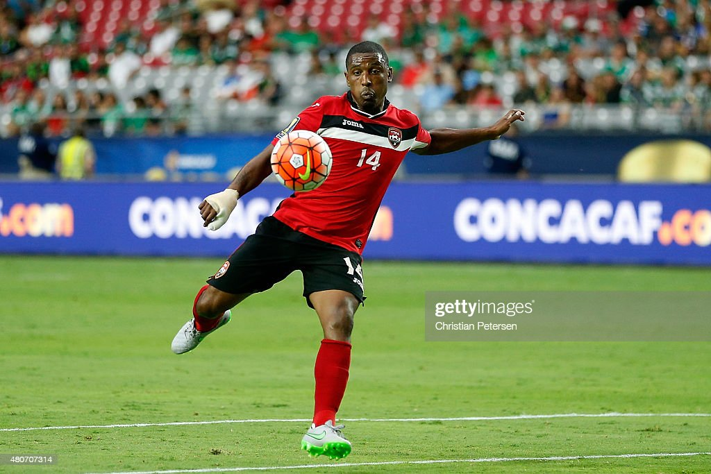 Andre Boucaud of Trinidad Tobago shoots the ball during the 2015 CONCACAF Gold Cup group C match against Cuba at University of Phoenix Stadium on...