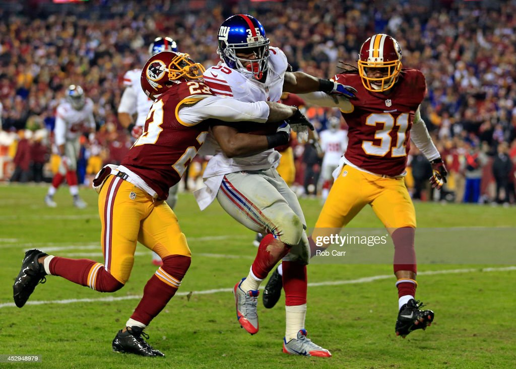 Andre Brown of the New York Giants runs the ball in for a touchdown in the second quarter against DeAngelo Hall and Brandon Meriweather of the...