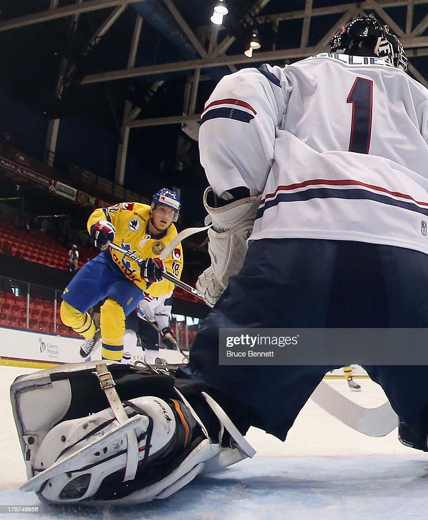 Andre Burakowsky #18 of Team Sweden takes the shot against Jon Gillies #1 of Team USA during the 2013 USA Hockey Junior Evaluation Camp at the Lake Placid Olympic Center on August 7, 2013 in Lake Placid, New York. Sweden shut out the USA