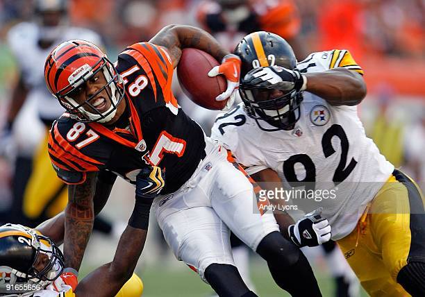 Andre Caldwell of the Cincinnati Bengals runs with the ball while defended by Deshea Townsend and James Harrison of the Pittsburgh Steelers at Paul...
