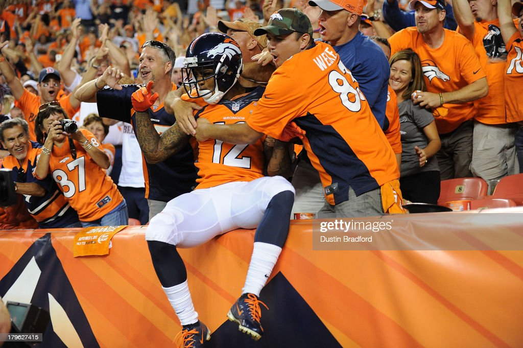 Andre Caldwell #12 of the Denver Broncos celebrates with fans in the first row of seats in the back of the end zone after catching a 28-yard touchdown pass against the Baltimore Ravens in the third quarter during the game at Sports Authority Field at Mile High on September 5, 2013 in Denver Colorado.