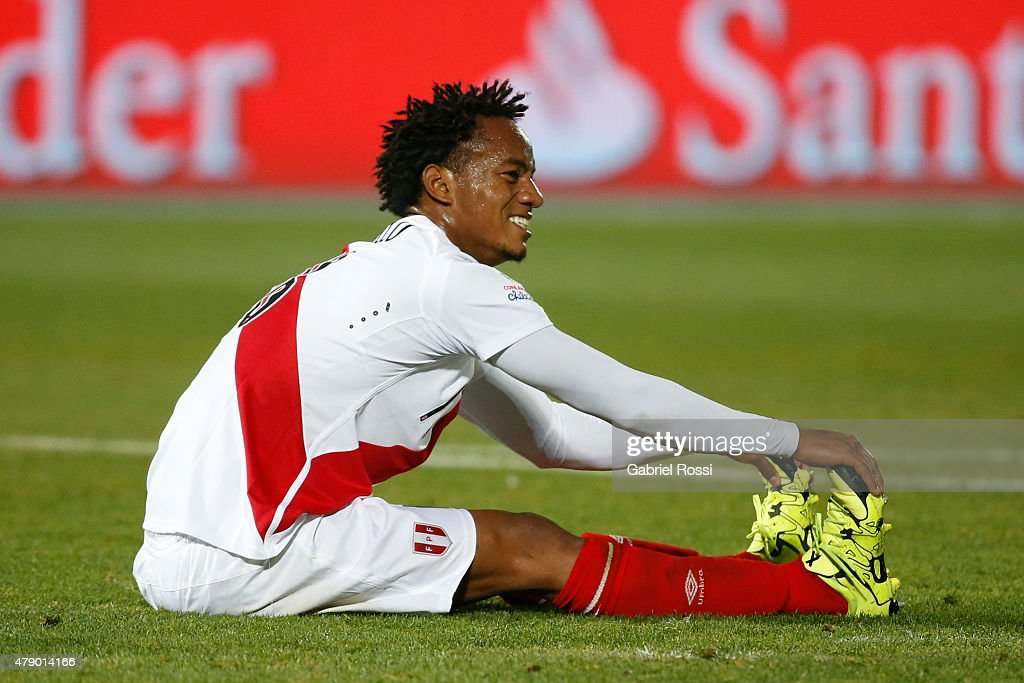 Andre Carrillo of Peru lies on the grass during the 2015 Copa America Chile Semi Final match between Chile and Peru at Nacional Stadium on June 29, 2015 in Santiago, Chile.