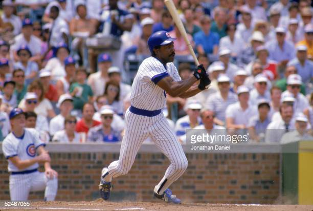 Andre Dawson of the Chicago Cubs watches the flight of the ball as he follows through on his swing during a game in 1989 at Wrigley Field in Chicago...