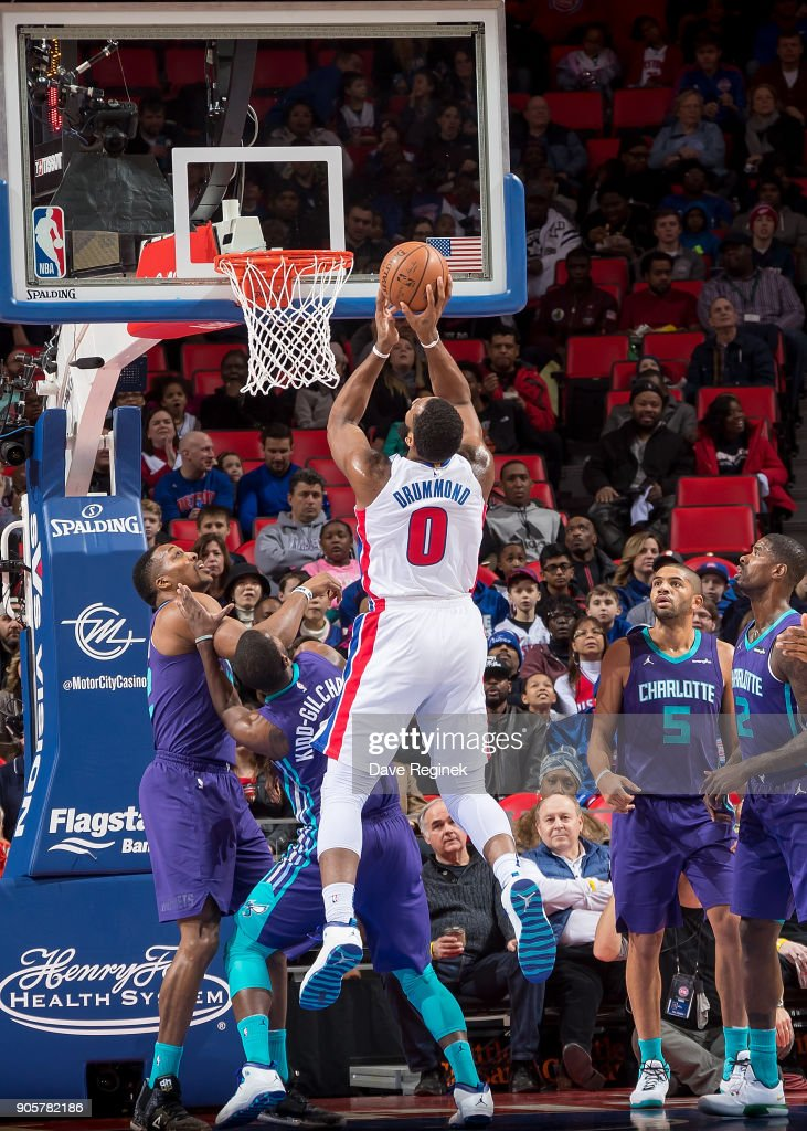 Andre Drummond #0 of the Detroit Pistons drives to the basket over Dwight Howard #12 and Michael Kidd-Gilchrist #14 of the Charlotte Hornets during the an NBA game at Little Caesars Arena on January 15, 2018 in Detroit, Michigan.