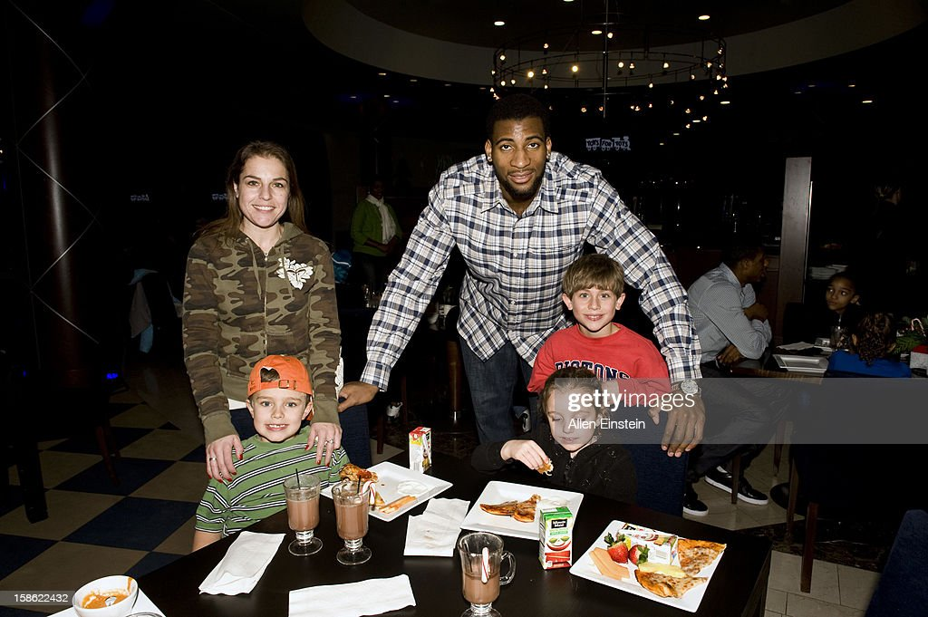 Andre Drummond of the Detroit Pistons, interacts with a family during the Detroit Pistons Toys for Tots Holiday event for metro Detroit families at the Palace of Auburn Hills on December 20, 2012 in Auburn Hills, Michigan.