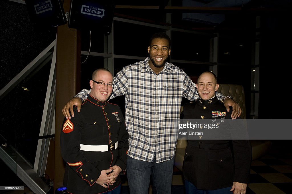 Andre Drummond of the Detroit Pistons, poses with two U.S. Marines during the Detroit Pistons Toys for Tots Holiday event for metro Detroit families at the Palace of Auburn Hills on December 20, 2012 in Auburn Hills, Michigan.