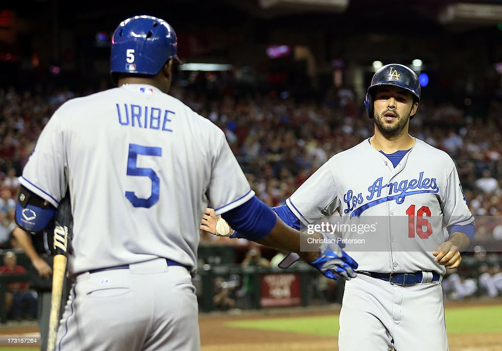 Andre Ethier #16 of the Los Angeles Dodgers high-fives Juan Uribe #5 after scoring against the Arizona Diamondbacks during the seventh inning of the MLB game at Chase Field on July 8, 2013 in Phoenix, Arizona.