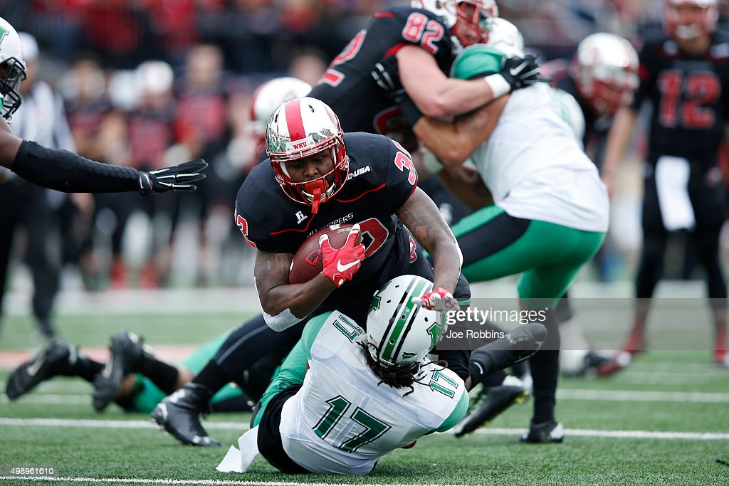 Andre Ferby of the Western Kentucky Hilltoppers runs for a first down against Taj Letman of the Marshall Thundering Herd in the first half of the...