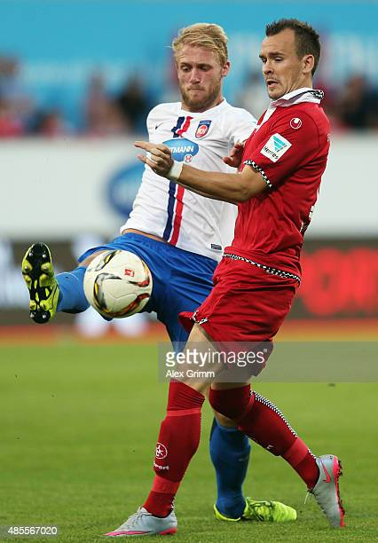 Andre Fomitschow of Kaiserslautern is challenged by Sebastian Griesbeck of Heidenheim during the Second Bundesliga match between 1 FC Heidenheim and...