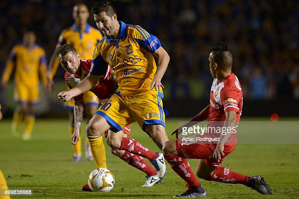 Andre Gignac of Tigres fights for the ball with Dario Botinelli and Christian Cueva of Toluca during the semifinals first leg match between Tigres...