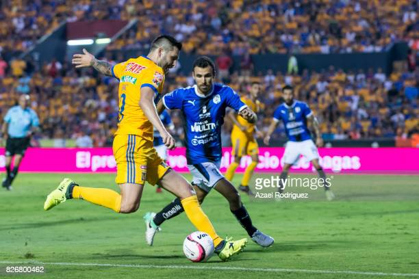 Andre Gignac of Tigres fights for the ball with Jonathan Bornstein of Queretaro during the 3rd round match between Tigres UANL and Puebla as part of...
