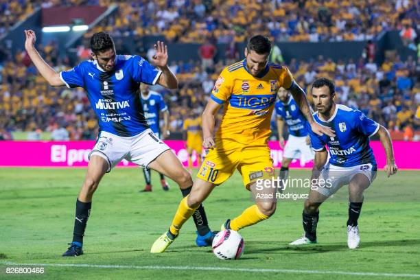 Andre Gignac of Tigres fights for the ball with Paolo Yrizar and Jonathan Bornstein of Queretaro during the 3rd round match between Tigres UANL and...