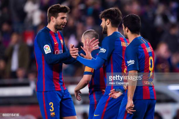 Andre Gomes of FC Barcelona celebrates with his teammate Gerard Pique after scoring his team's fourth goal during the La Liga match between FC...