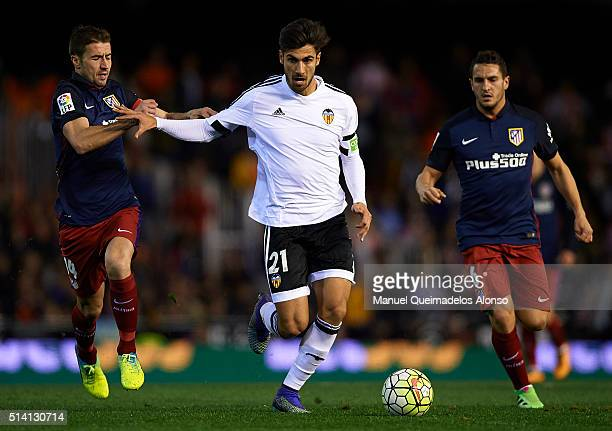Andre Gomes of Valencia competes for the ball with Gabi of Atletico de Madrid during the La Liga match between Valencia CF and Atletico de Madrid at...