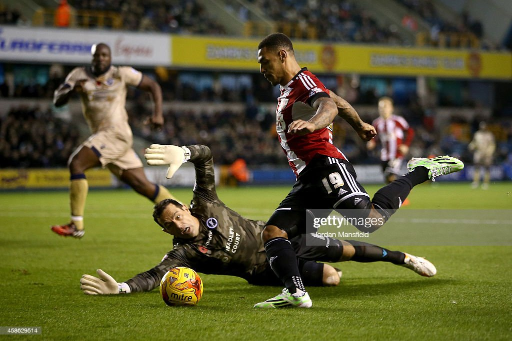 Andre Gray of Brentford gets past Millwall goalkeeper David Forde during the Sky Bet Championship match between Millwall and Brentford at The Den on November 8, 2014 in London, England.