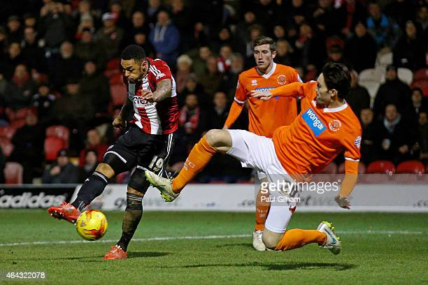 Andre Gray of Brentford scores his team's third goal despite the diving challenge from Connor Oliver of Blackpool during the Sky Bet Championship...