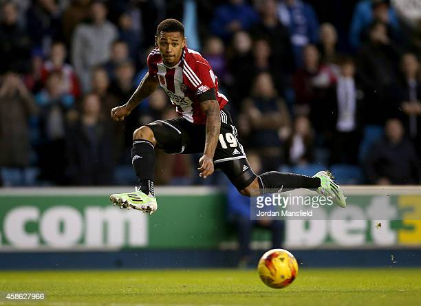Andre Gray of Brentford takes a shot on goal during the Sky Bet Championship match between Millwall and Brentford at The Den on November 8 2014 in...