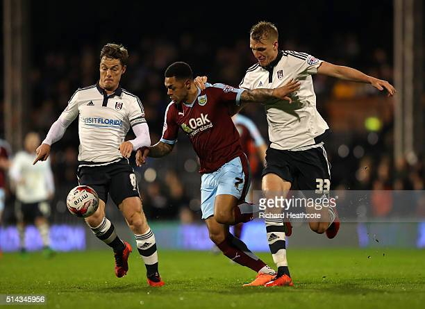 Andre Gray of Burnley is tackled by Scott Parker and Dan Burn of Fulham during the Sky Bet Championship match between Fulham and Burnley at Craven...