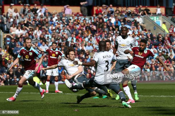 Andre Gray of Burnley shoots at goal past Daley Blind and Eric Bailly of Manchester United during the Premier League match between Burnley and...