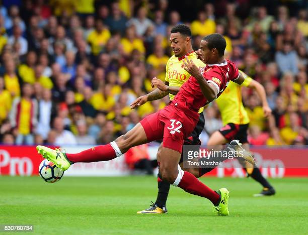 Andre Gray of Watford is tackled by Joel Matip of Liverpool during the Premier League match between Watford and Liverpool at Vicarage Road on August...