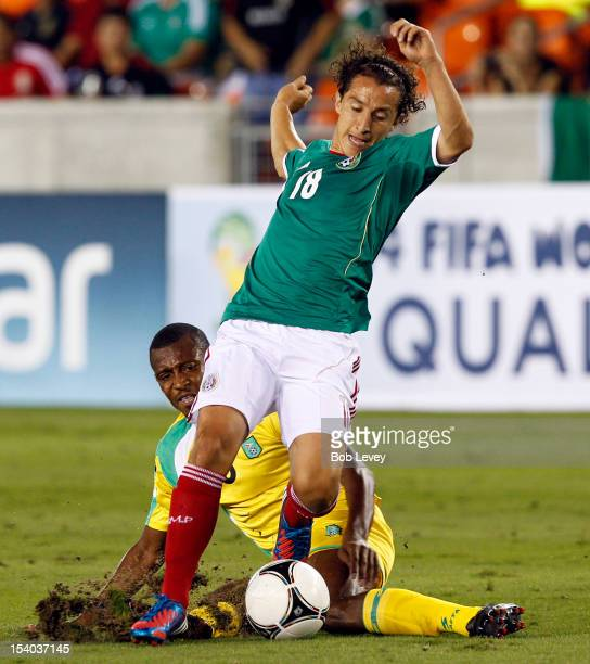 Andre Guardardo of Mexico is tackled from behind by Christopher Nurse of Guyana in the first half at BBVA Compass Stadium on October 12 2012 in...