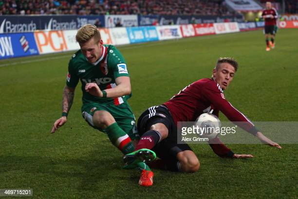 Andre Hahn of Augsburg is challenged by Ondrej Petrak of Nuernberg during the Bundesliga match between FC Augsburg and 1 FC Nuernberg at SGL Arena on...