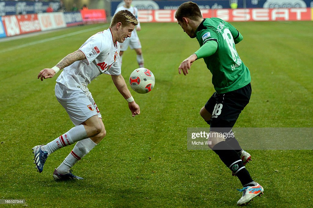 Andre Hahn (L) of Augsburg is challenged by <a gi-track='captionPersonalityLinkClicked' href=/galleries/search?phrase=Sebastien+Pocognoli&family=editorial&specificpeople=3942105 ng-click='$event.stopPropagation()'>Sebastien Pocognoli</a> of Hannover during the Bundesliga match between FC Augsburg and Hannover 96 at SGL Arena on March 30, 2013 in Augsburg, Germany.