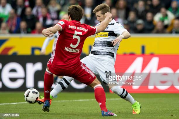 Andre Hahn of Borussia Moenchengladbach and Mats Hummels of FC Bayern Muenchen battle for the ball during the Bundesliga Match between Borussia...
