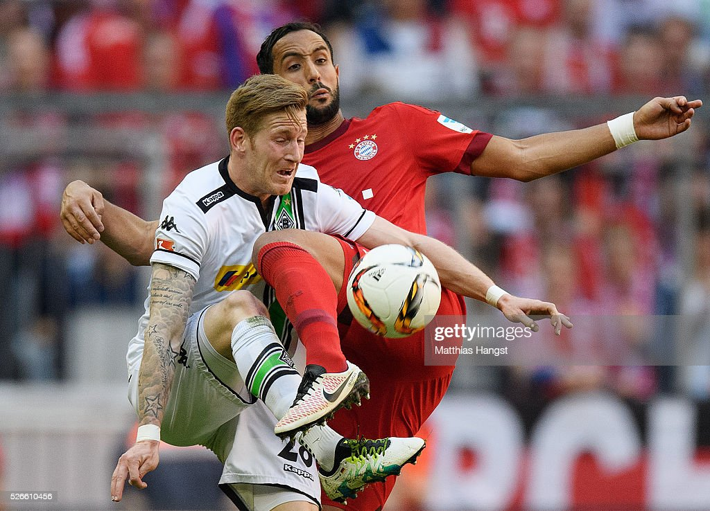Andre Hahn of Borussia Moenchengladbach and Medhi Benatia of Bayern Muenchen compete for the ball during the Bundesliga match between FC Bayern Muenchen and Borussia Moenchengladbach at Allianz Arena on April 30, 2016 in Munich, Germany.