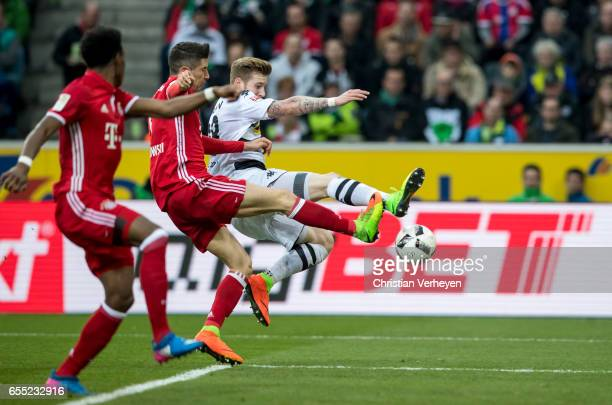 Andre Hahn of Borussia Moenchengladbach and Robert Lewandowski of FC Bayern Muenchen battle for the ball during the Bundesliga Match between Borussia...