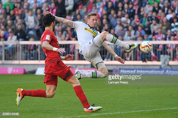 Andre Hahn of Borussia Moenchengladbach and Serdar Tasci of Bayern Muenchen compete for the ball during the Bundesliga match between Bayern Muenchen...